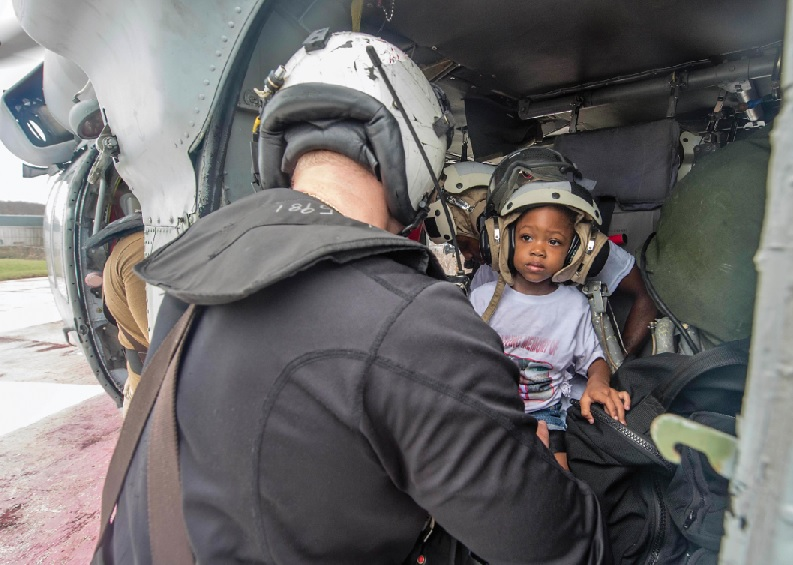 Naval Aircrewman (Helicopter) 2 nd Class Logan Parkinson, assigned to Helicopter Sea Combat Squadron (HSC) 22, prepares a patient's family for evacuation during relief efforts in the wake of Hurricane Maria in the U.S. Virgin Islands, Sept. 21. U.S. Navy MC3 Levingston Lewis Photo
