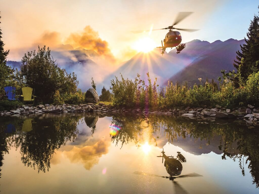 Maur Mere's grand-prize-winning photo of an Airbus AS350 AStar perfectly reflected in a still mountain pond as it takes off to begin firefighting operations in British Columbia. Maur Mere Photo