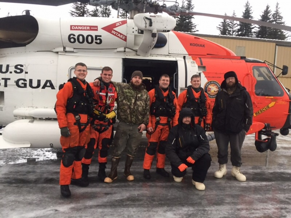 A Coast Guard Air Station Kodiak MH-60 helicopter crew pose with the three men they rescued from Chenega Island, Alaska, on Jan. 1, 2018. The three men went missing on Dec. 29 in Prince William Sound after experiencing mechanical problems on their 20-foot Duckworth jet boat. Coast Guard air and boat crews searched over 1,600 square miles in harsh weather conditions before locating the missing men. U.S. Coast Guard Photo