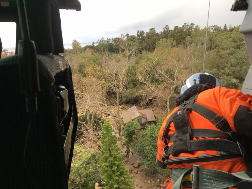 A crewmember looks out of a Coast Guard MH-65 helicopter during the mudslide response on Jan. 9.
