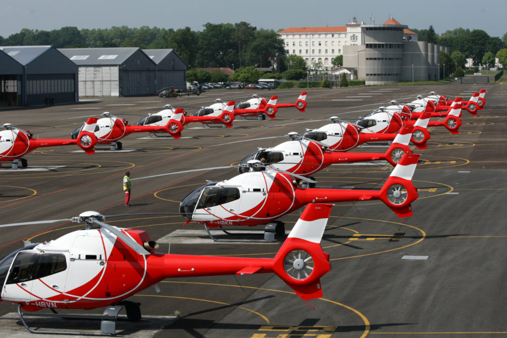 Several red and white helicopters rest on ground