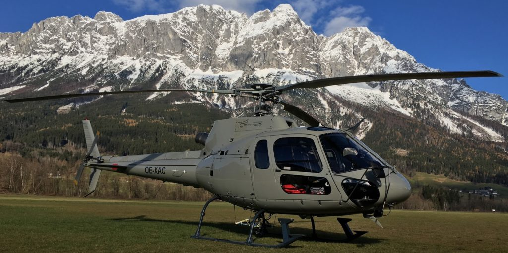 Helicopter rests on ground, with mountains in background.