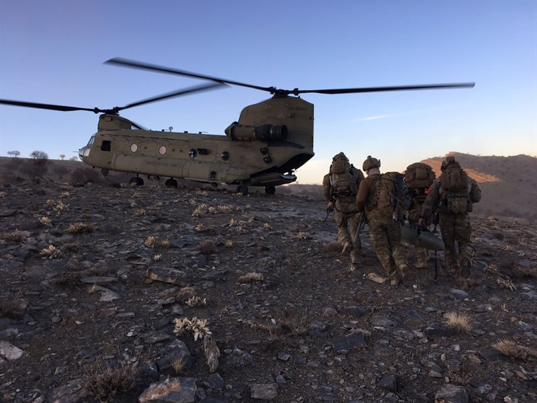 Members of the 83rd Expeditionary Rescue Squadron prepare to board a U.S. Army CH-47 Chinook at an undisclosed location in Afghanistan.