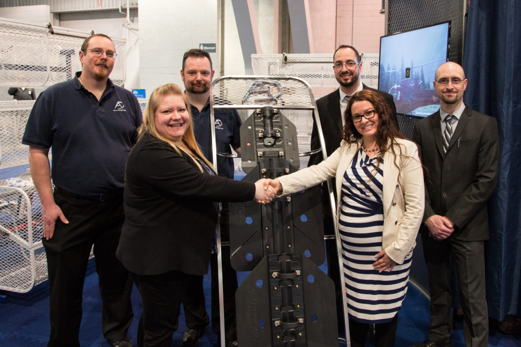Team members from Aero Design and Helitowcart celebrate the acquisition in front of a stand of Bearpaws at HAI Heli-Expo 2018. Aero Design Photo