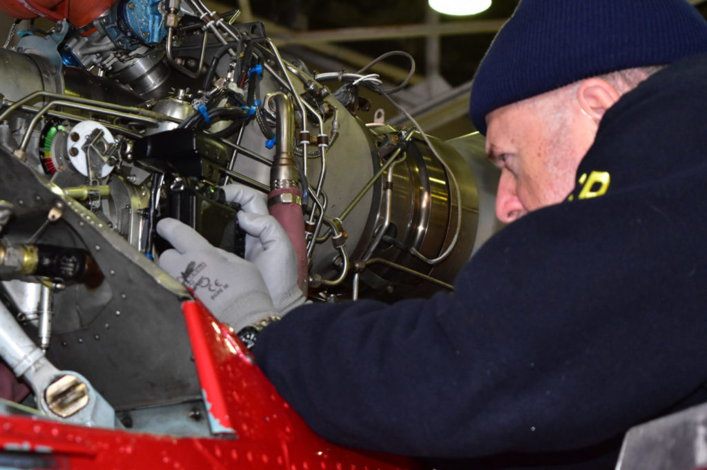 Harald Reichel of the NTSB's Office of Aviation Safety examines the engine of a Liberty Helicopters AS30 B2 that crashed in the East River on March 11, 2018. Chris O'Neil/NTSB Photo