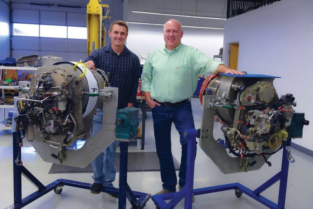 ITS owner Darryl Christensen (right) stands with his son Brad Christensen, ITS's quality manager, behind the LTS101 and HTS900 engines. Mike Reyno Photo
