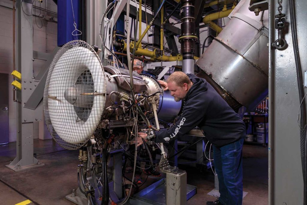 John Chergosky connects test leads to one of the S-64's P&WC JFTD12A turboshaft engines in Erickson's engine test cell. Heath Moffatt Photo