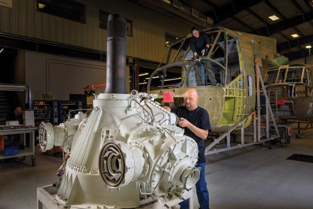 Tory Grussling checks fittings on the main rotor gear box and mast assembly of an S-64. Heath Moffatt Photo