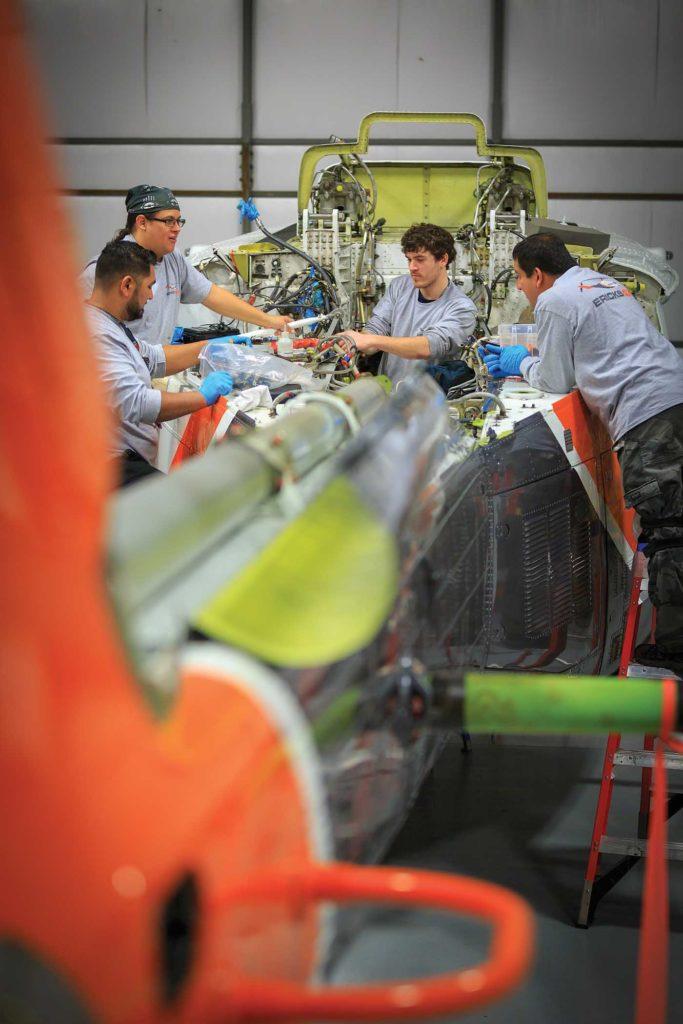 Aviation mechanics Melvin Soloranzo, Mingan Kijika, Mike Patz, and Charles Ayala work on a Bell 214ST. Heath Moffatt Photo