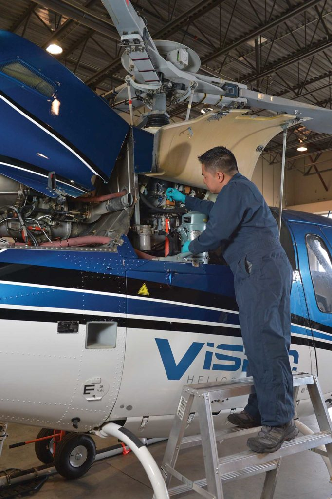 Aeromni's quality assurance manager, Brian Carandang, performs maintenance on an Airbus AS350 B2 operated by Vancouver-based Vision Helicopters. Charlie Vowles Photo