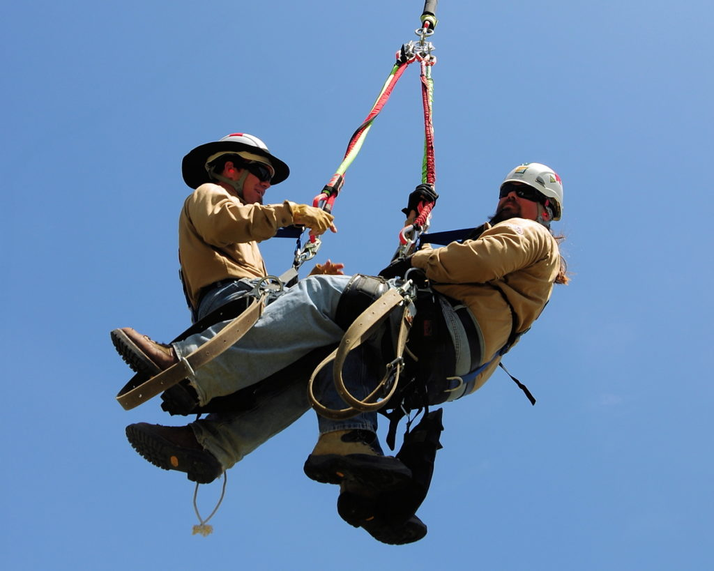 Two power linemen are flown on a line beneath a helicopter