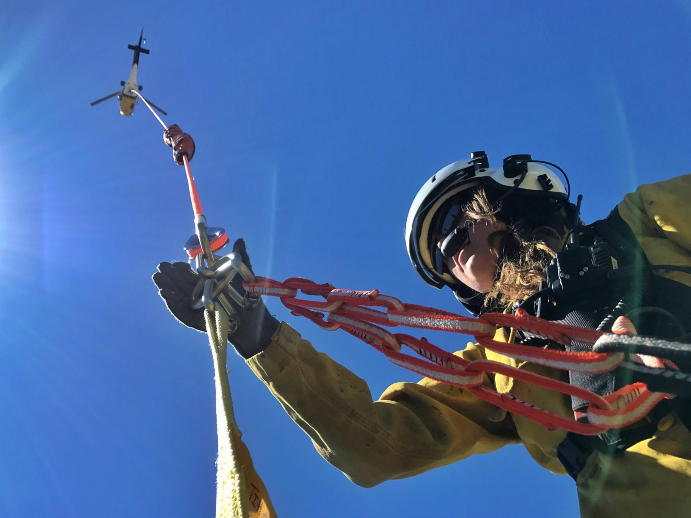 A Forest Service short-hauler prepares to be lifted by a helicopter