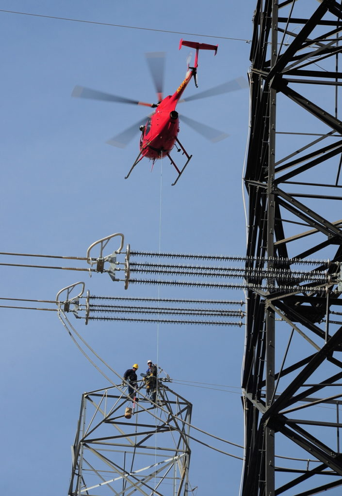 A helicopter hovers above line technicians on a transmission tower