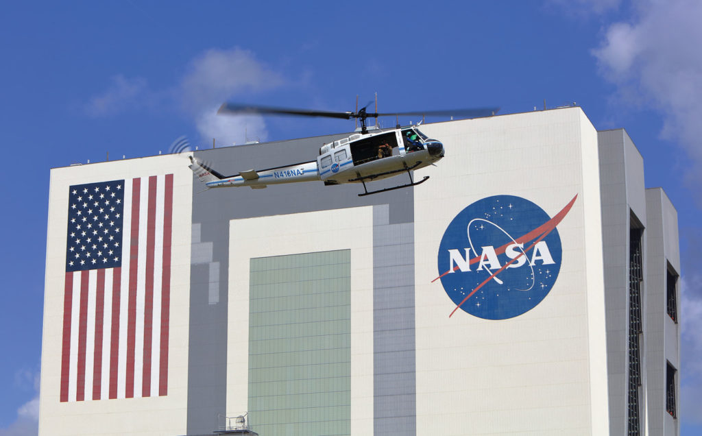 A NASA Bell UH-1H Huey II flies past the historic Vehicle Assembly Building at the Kennedy Space Center in Florida. Alan Walters Photo