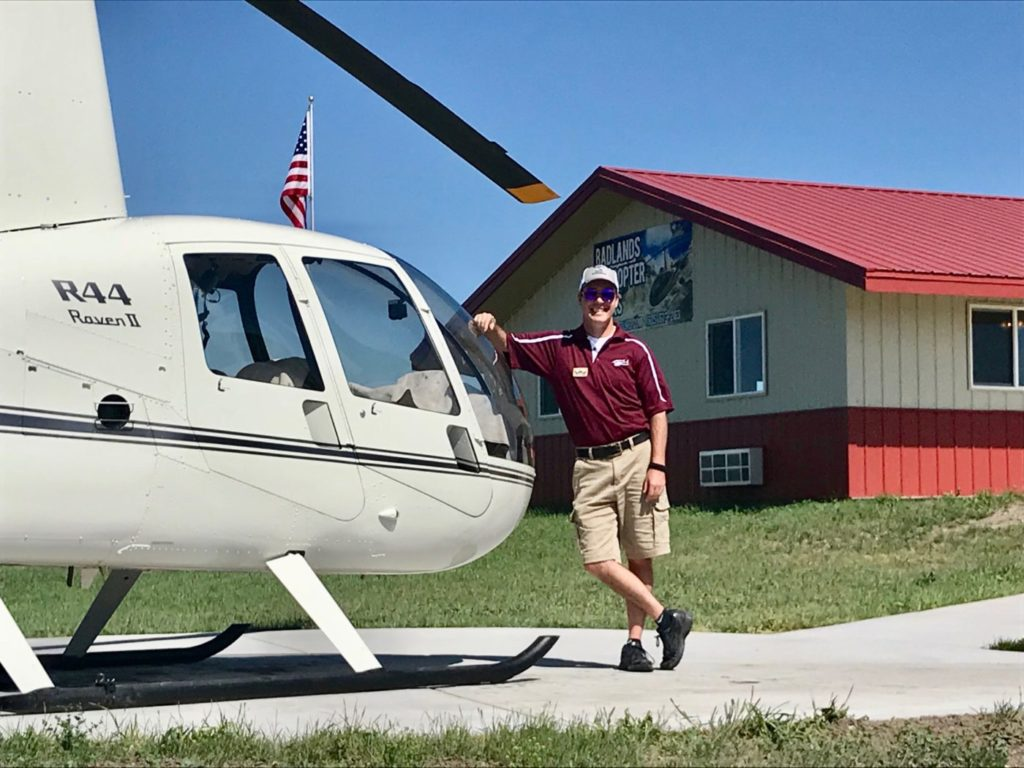 A pilot poses next to a Robinson R44 helicopter