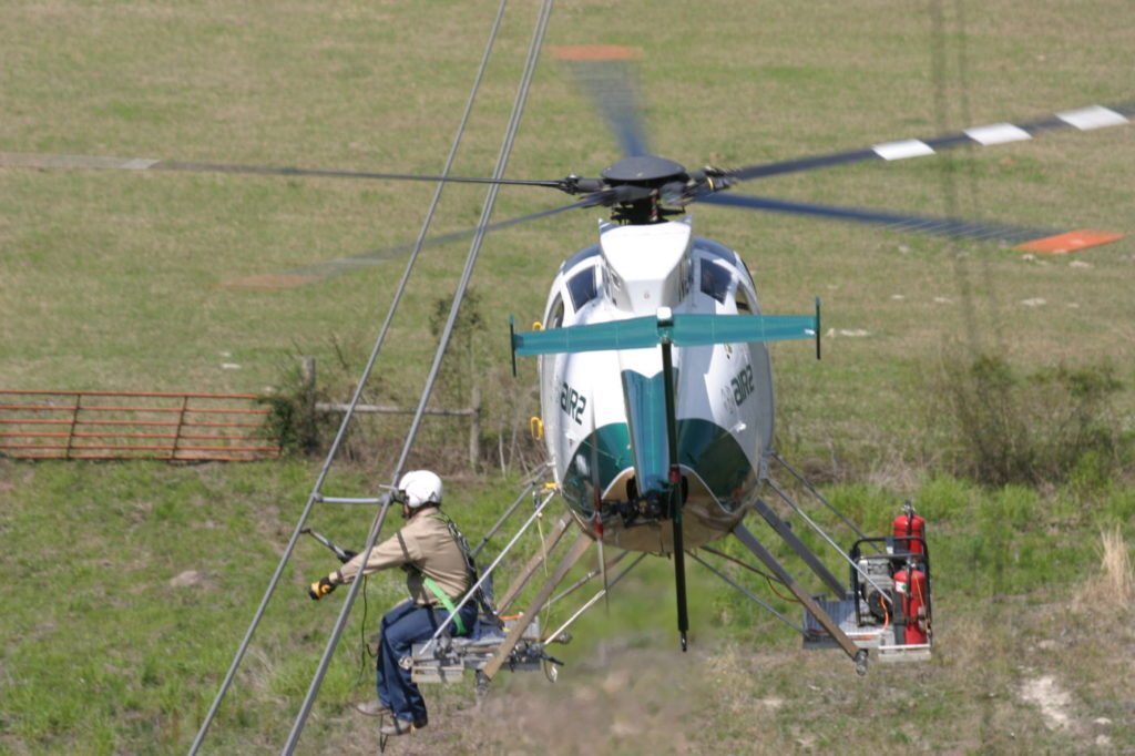 A power line technician works off the skid of an Air2 helicopter