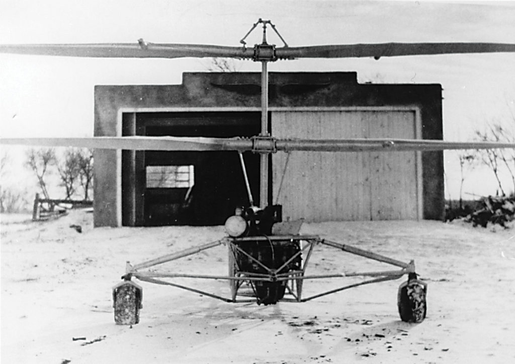 A front view of the Froebe helicopter in front of a farm building. Note the small fuel tank on the side of the engine. Royal Aviation Museum of Western Canada Photo