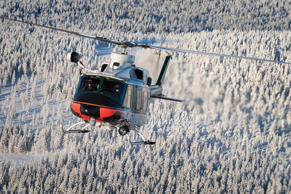 Exhaust pours from the engines of a Finnish Border Guard Bell 412 as its crew flies above the most dominant features of Rovaniemi landscape, snow and trees. Lloyd Horgan Photo