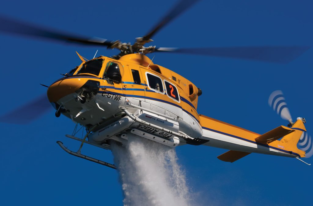 A Bell 412 operated by Wisk Air Helicopters demonstrates a water drop with its 375-gallon (1,420-liter) Simplex Belly Tank. The aircraft is one of three 412s in the operator's fleet, and is working on a major firefighting contract this summer. Mike Reyno Photo