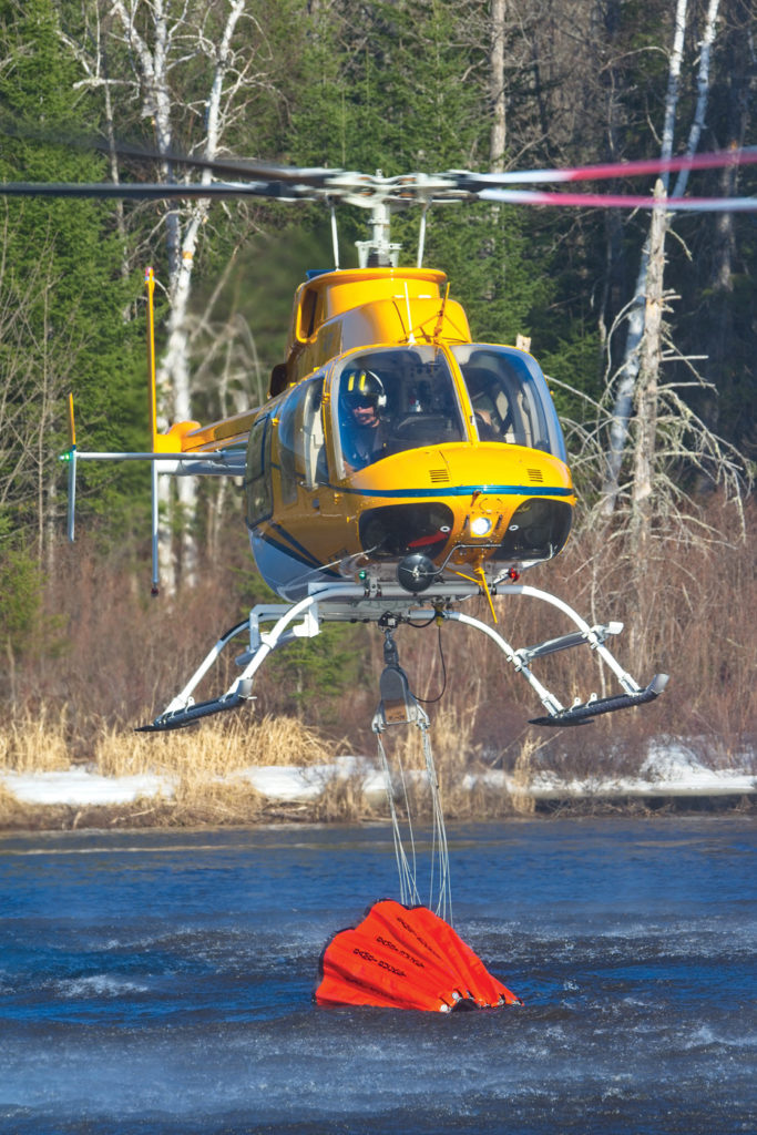 Firefighting work is typically performed on the company's Bell 412s, but it has a range of Bambi buckets to allow its entire fleet to fight wildfires when needed. Here, a Bell 407 fills a bucket in a river. Mike Reyno Photo