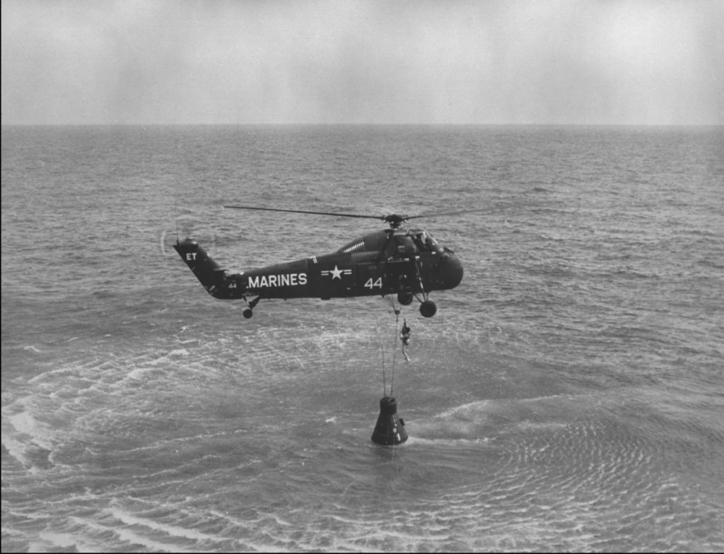 NASA Astronaut Alan B. Sheppard Jr. is hoisted up in a body harness by a U.S. Marin Corps helicopter recovery team following the first Project Mercury suborbital space flight. NASA Photo