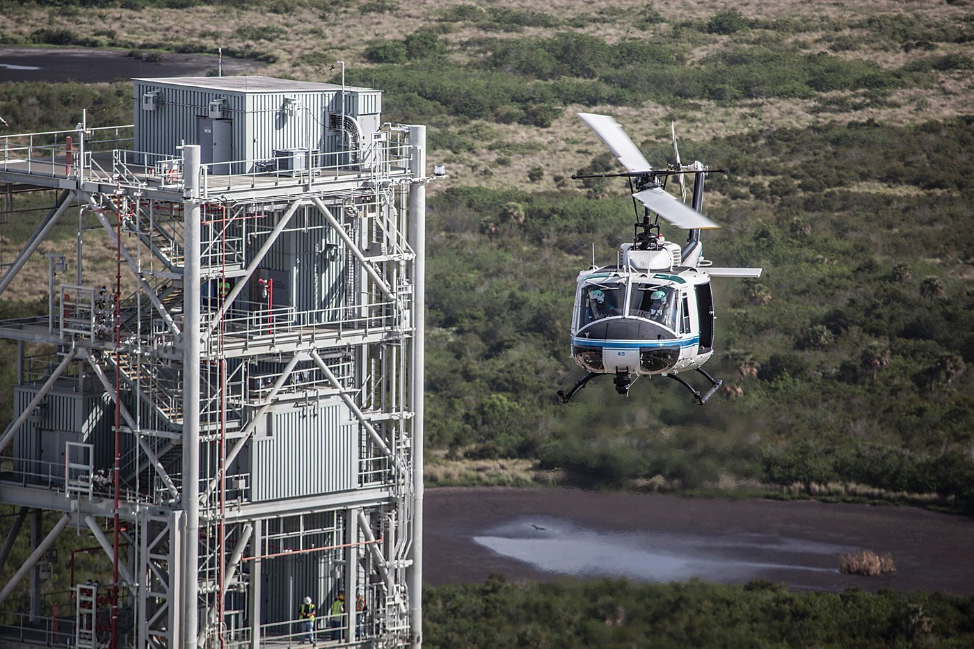 "During an early morning training exercise for aircraft operations pilots at the Kennedy Space Center, a NASA UH-1 ""Huey"" helicopter flies past the Mobile Launcher that will be used for the agency's new Space Launch System rocket. The new launch vehicle will send humans to deep-space destinations such as a near-Earth asteroid or Mars. The center's helicopter operations support numerous missions at the multi-user spaceport. NASA/Kim Shiflett Photo"