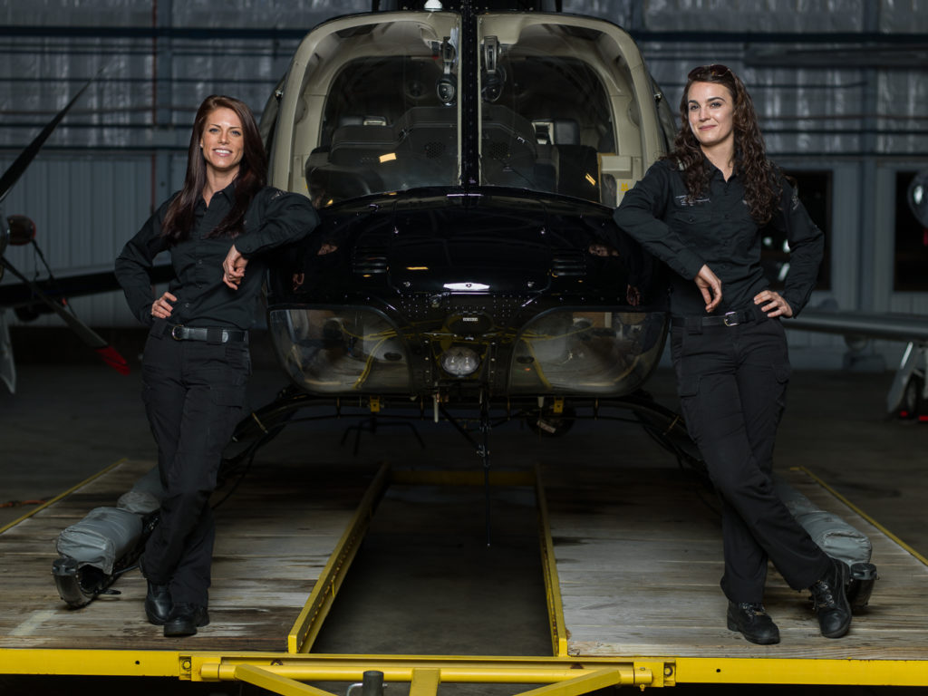 Helicopter pilots Autumn Cabaniss (left) and Melissa Winterborn (right) lean against a Bell 407 sitting on a helicopter dolly. Aviatrix Life Photo