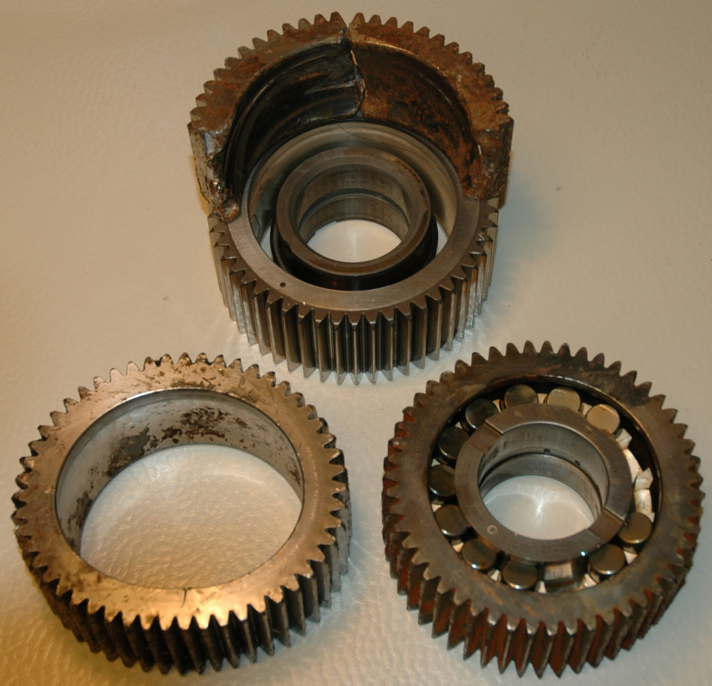 Recovered parts from the accident aircraft's second stage planet gear. Parts of the failed gear have been placed on top of a sample gear. AIBN Photo
