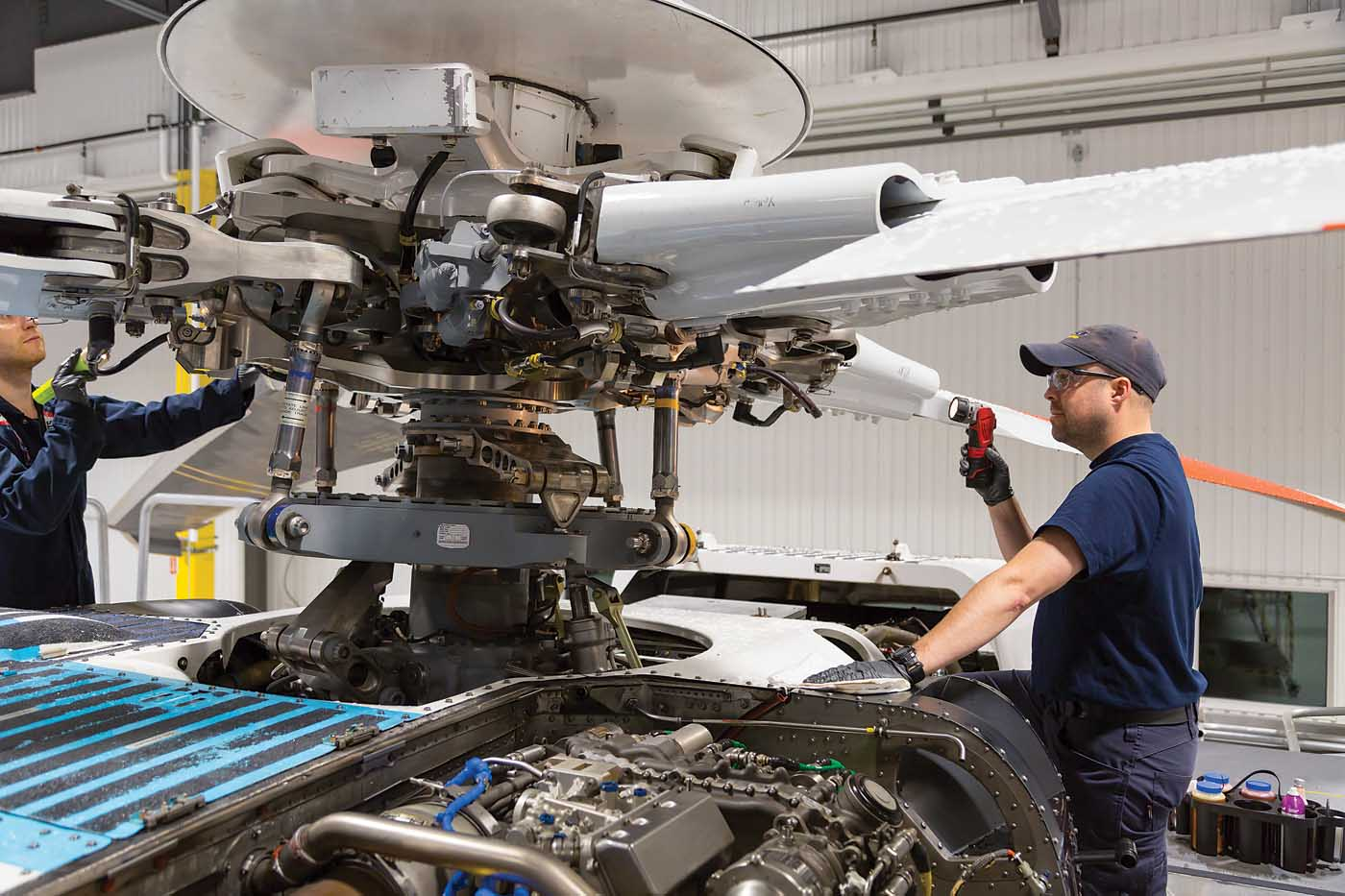 Maintenance engineers inspect the main rotor hub of a Sikorsky S-92. The manufacturer has used HUMS data to extend the part's service life in the past, and is now using that data to predict negative events. Heath Moffatt Photo