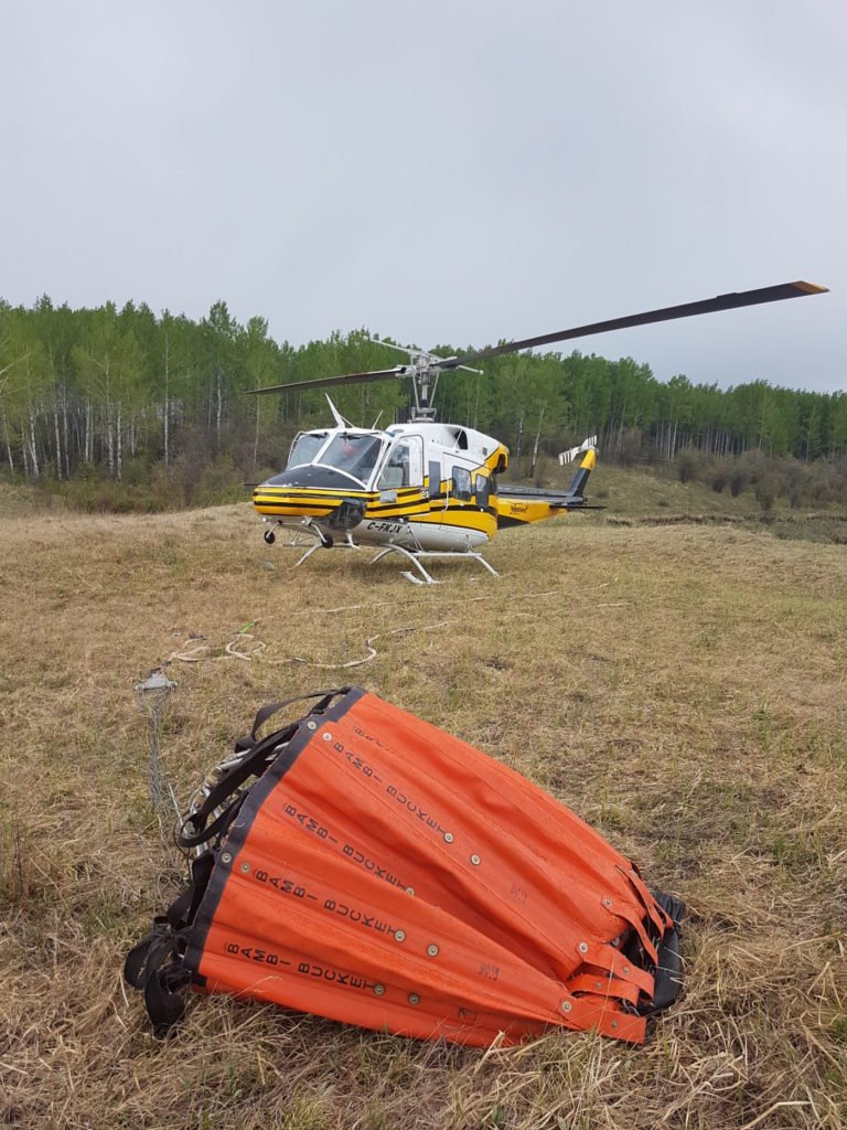 Here, a Yellowhead Helicopters Bell 212HP sits near Pink Mountain, British Columbia, with its Bambi Bucket. Yellowhead Helicopters Photo
