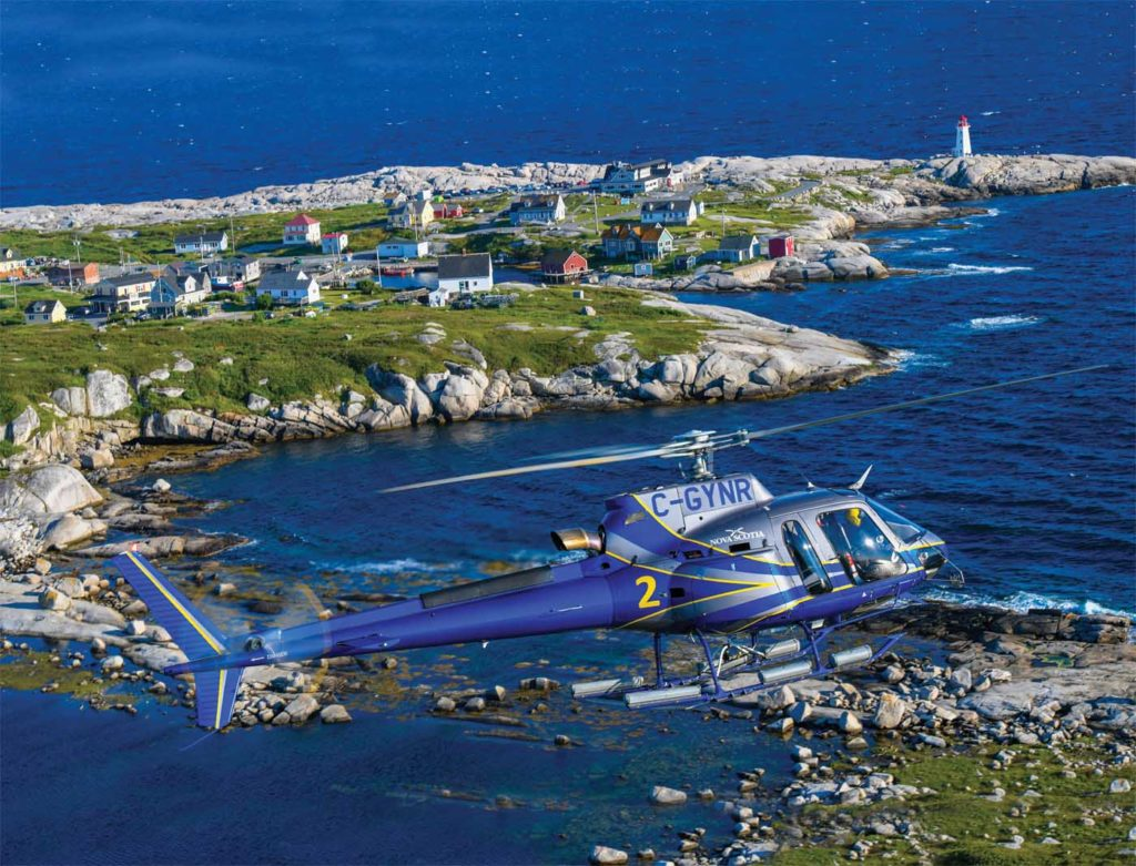 An Airbus H125 AStar, operated by Nova Scotia's Department of Lands and Forestry, Aviation Services, flies alongside the popular fishing village of Peggy's Cove in Nova Scotia. Mike Reyno Photo