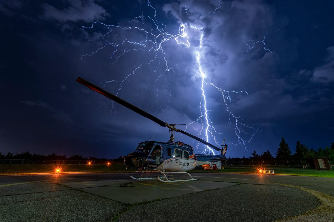 A Bell 205 sits on a helipad in Prince Albert, Saskatchewan, as lightning strikes in the background. Photo submitted by Dean Johnson