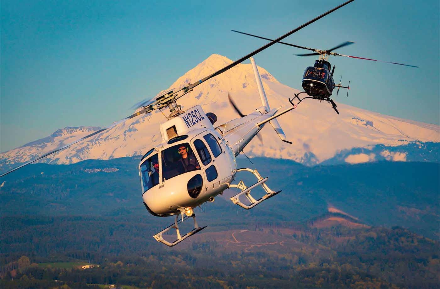An Airbus H125 and Bell 407 operated by Hillsboro Aviation fly in front of Mount Hood in northern Oregon. Now celebrating 38 years in operation, the company continues to evolve alongside the industries it serves. Heath Moffatt Photo