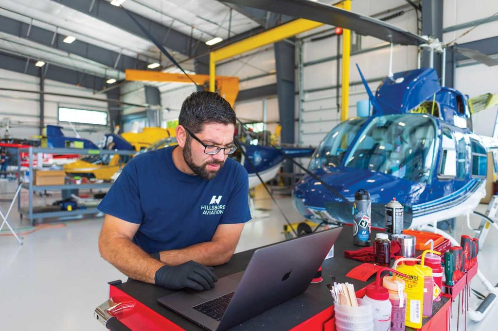 Mechanic Joshua Knowlton at the computer during a visual inspection of a Bell 206. Heath Moffatt Photo
