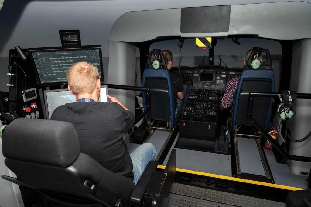 An instructor station is positioned behind the cockpit module in the AW139 helicopter simulator.