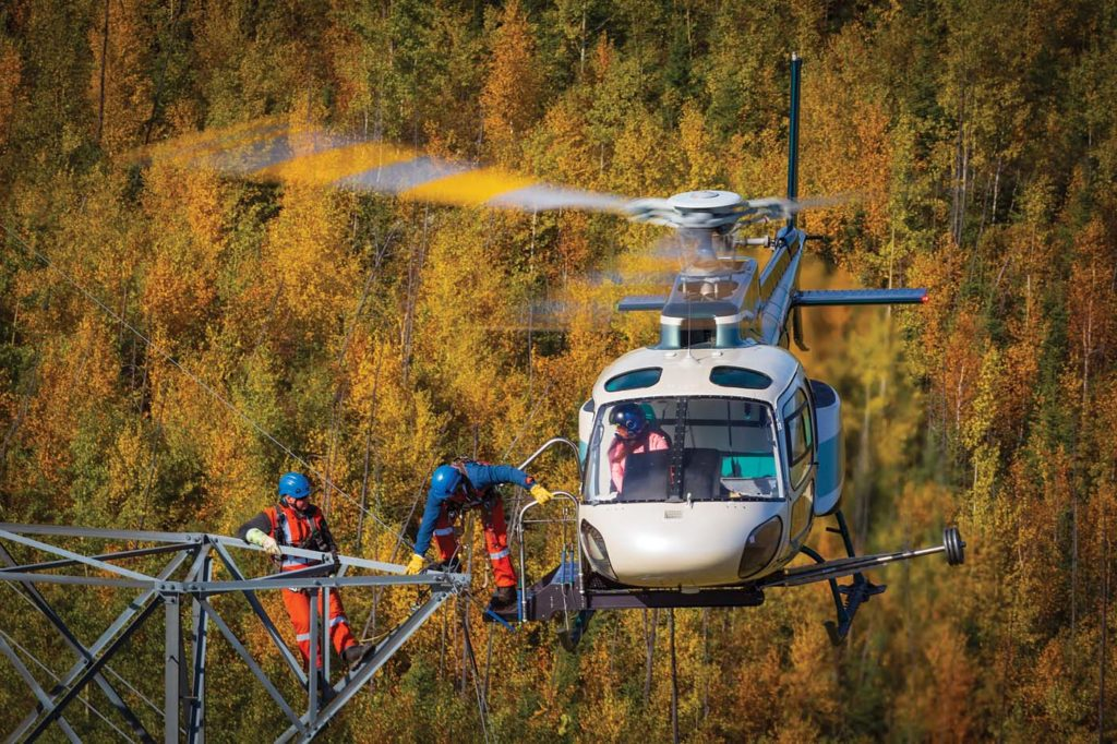 A lineman completes a transfer onto a tower from Slave Lake Helicopters Airbus H125. The company uses its custom-designed AStep to perform these operations. Heath Moffatt Photo
