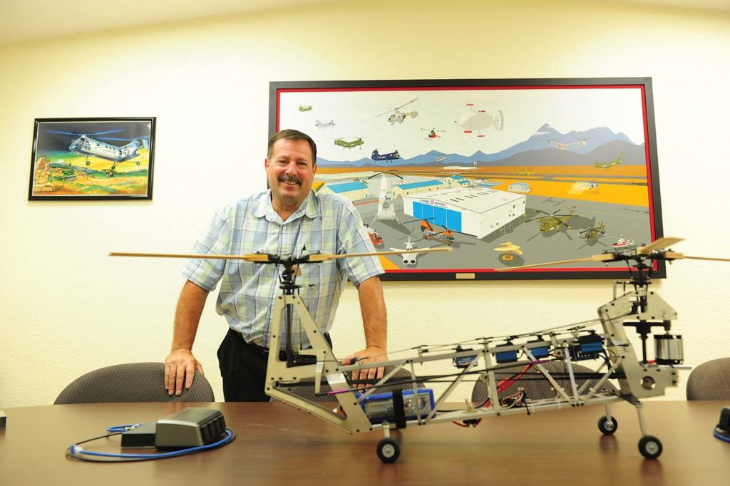 Mark DiCiero stands by a tandem rotor remote-controlled helicopter in front of a painting of the museum. His passion for helicopters, matched that of the museum's volunteers, has brought Classic Rotors to where it is today. Skip Robinson Photo