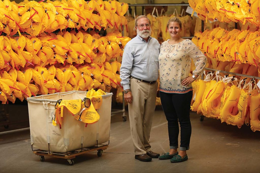 Stanley Switlik II, current owner of Switlik Survival Products, stands with his daughter Sarah Switlik, vice president of sales and marketing, among hundreds of Switlik life vests at the company's facility in Trenton, New Jersey. Switlik Photo