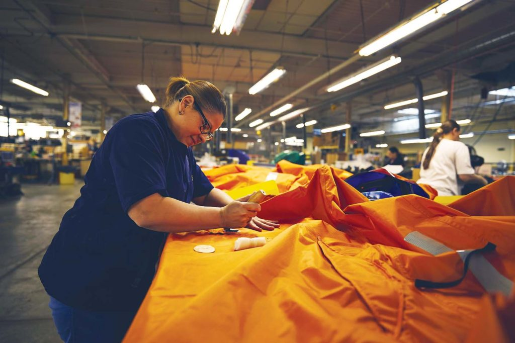 A staff member is shown constructing Switlik's unique convertible canopy for life rafts. The canopy allows raft users to keep the elements out in extreme weather conditions. Switlik Photo