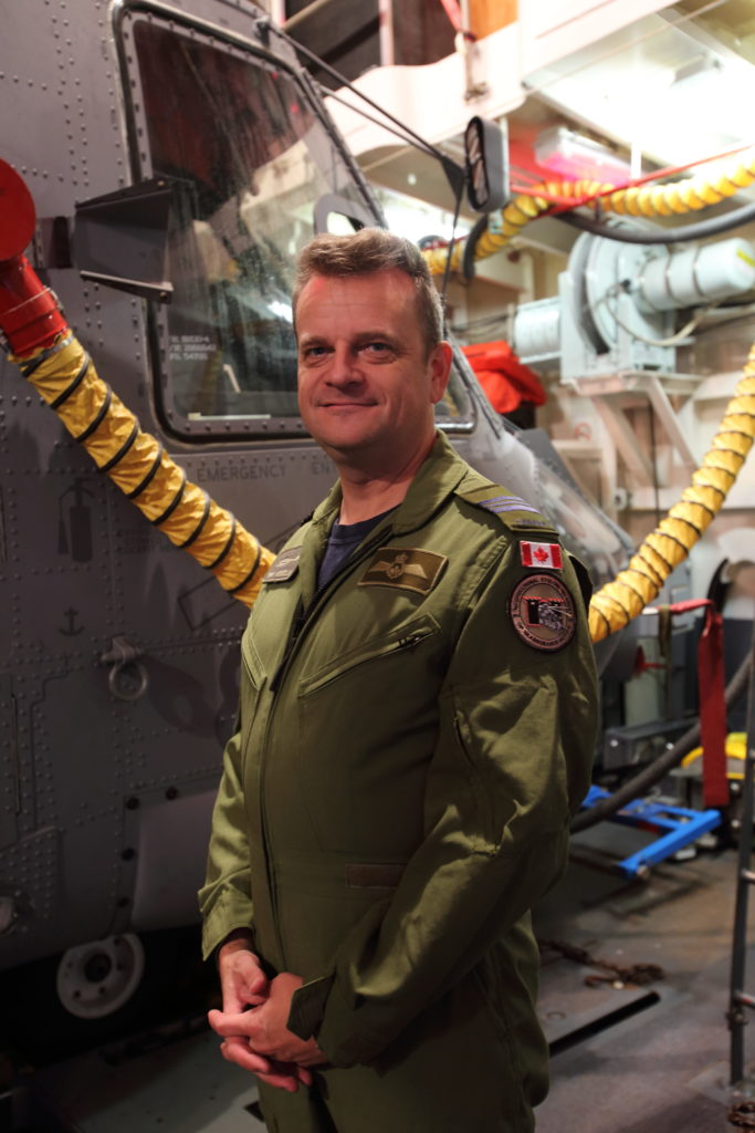 Maj Erik Weigelin stands with the Cyclone, wearing a badge on his arm that signifies the first CH-148 Cyclone to be deployed on an operational mission at sea. Patrick Dirksen and Frank Mink Photo
