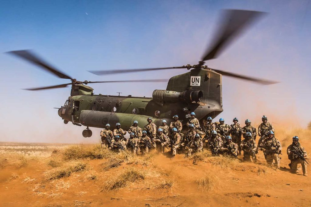 Members of Operation Presence-Mali pose for a group photo with a CH-147F Chinook at the small arms range near Gao in January. Cpl Ken Beliwicz Photo