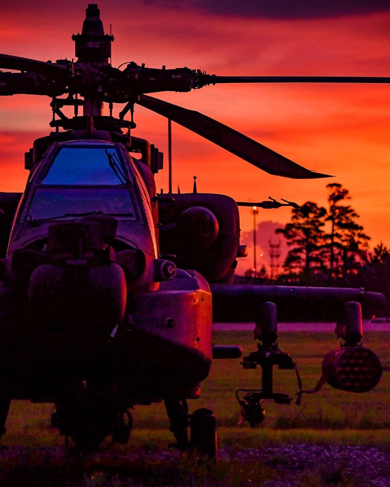 A Boeing AH-64 Apache is illuminated by the colors of a sunset. Photo submitted by @the_space_cowboy4 using #verticalmag