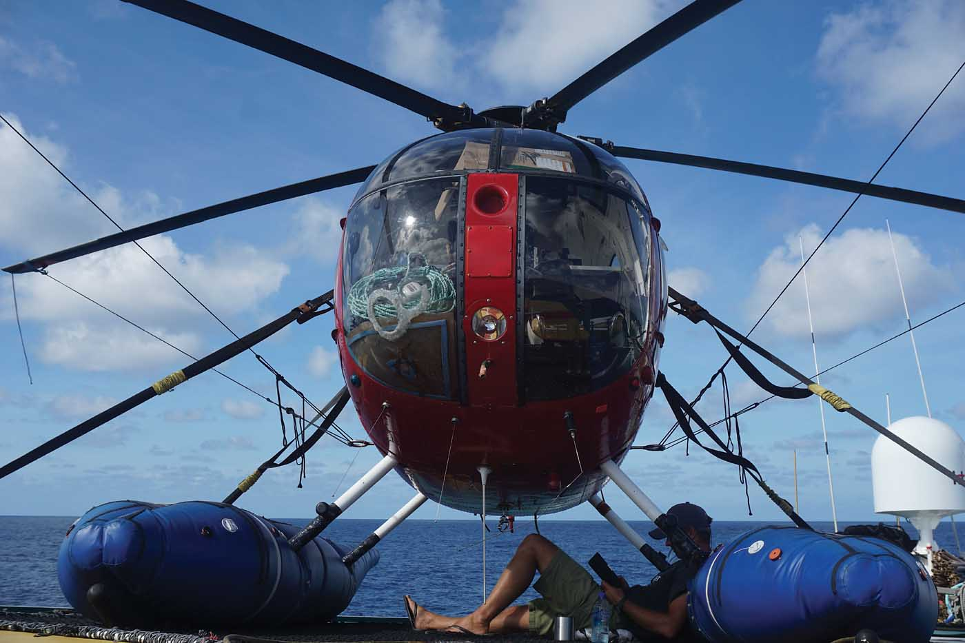 As a tuna boat helicopter pilot, there is plenty of time to sit back and relax. Here, the author rests under his MD 500 while reading a book. Matthew Hayes Photo