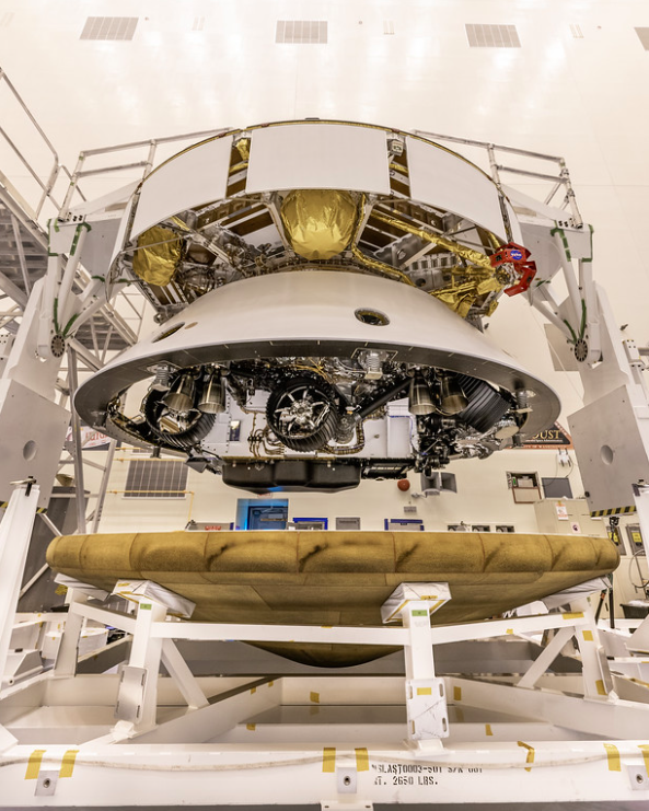 The Mars 2020 Perseverance rover mission's disk-shaped cruise stage sits atop the bell-shaped back shell, which contains the powered descent stage and Perseverance rover. Below is the brass-colored heat shield that is about to be attached to the back shell. NASA/JPL-Caltech/KSC Photo