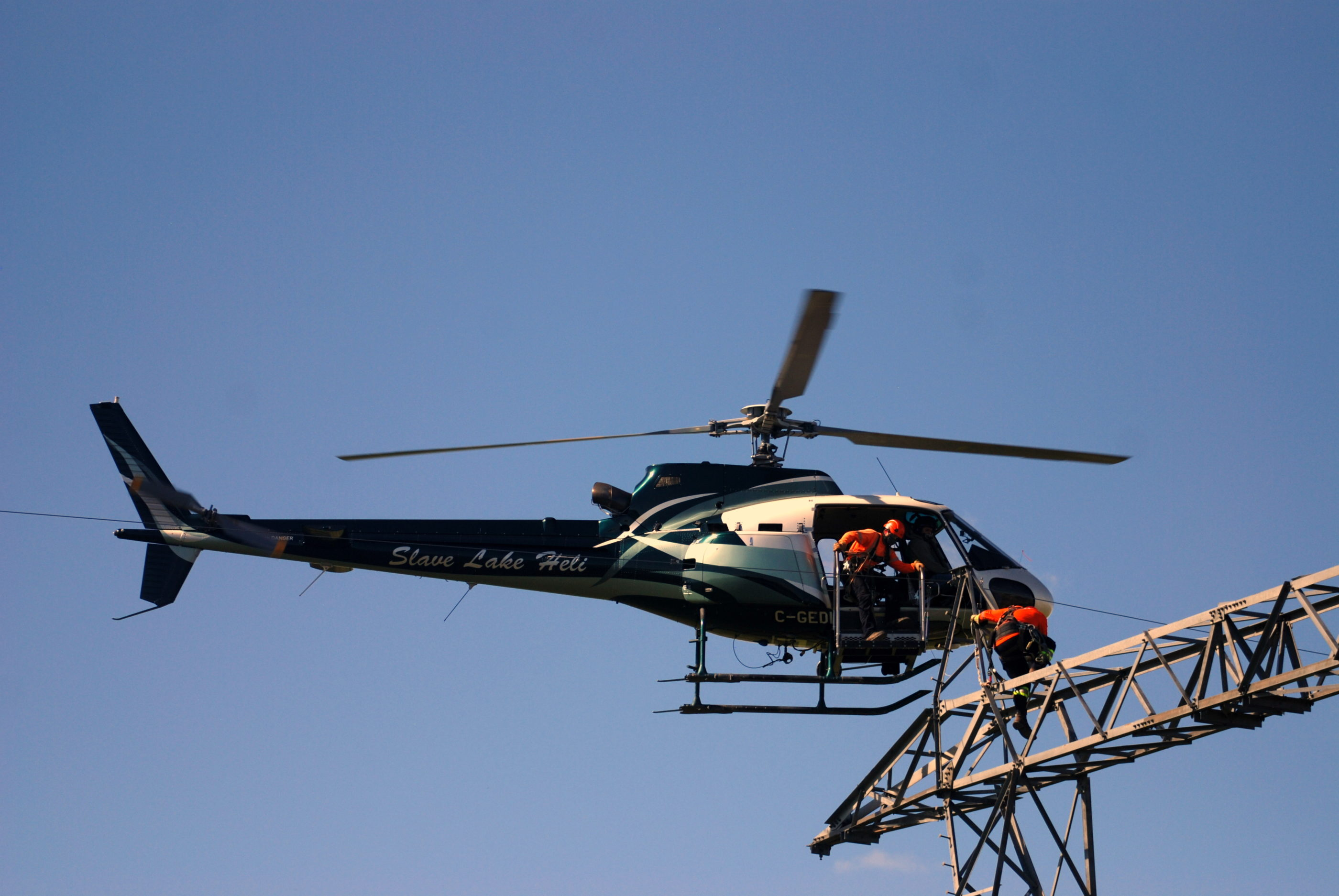 Slave Lake Helicopters Pilot Danny Ragan transfers powerline technicians. Slave Lake Helicopters Photo
