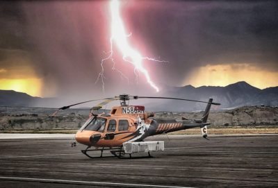 A Mountain Blade Runner Helicopters AS350 with a huge bolt of lightning in the background. Photo submitted by Instagram user @jmc280 using #verticalmag